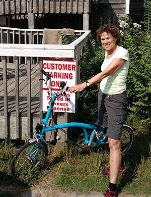 A woman poses with her blue bicycle.