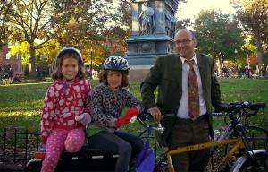 Un padre y sus hijas gemelas montan una bicicleta construida para tres.