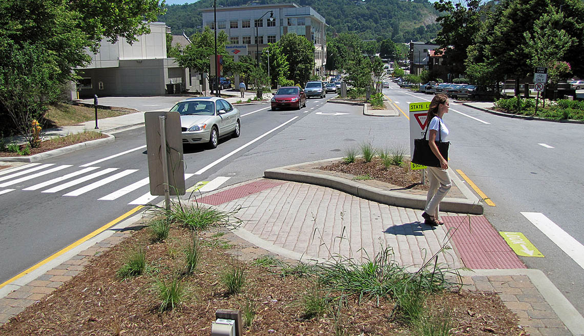 Woman At Crosswalk Island, Busy Street, Cars, Livability Index, Livable Communities