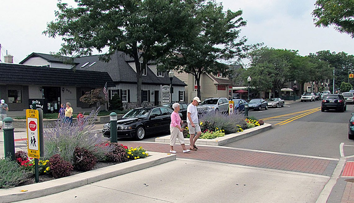 Elderly Couple Crosses A Crosswalk Through Town, Cars, In Livable Communities Slideshow