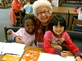 An older woman and two pre-school girls take a break from reading at a library.