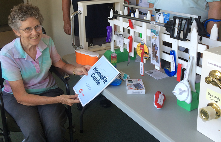 A woman sits at a display of handy household tools, including the AARP HomeFit Guide.