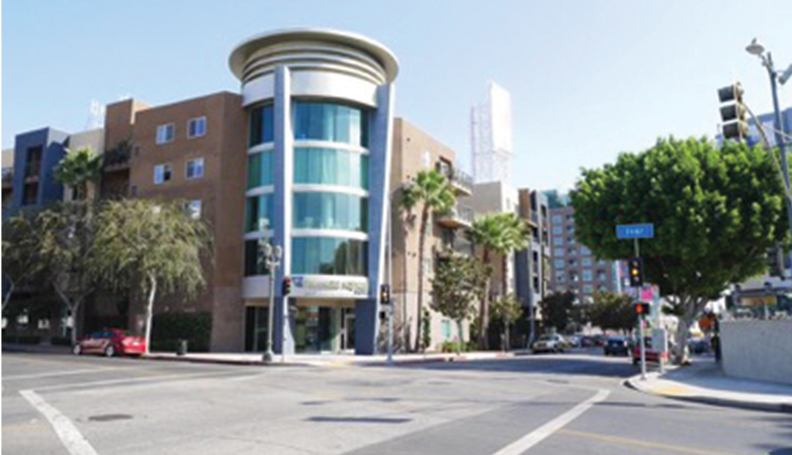 City Intersection looking toward a building with a circular glass tower on corner and palm trees on sidewalk