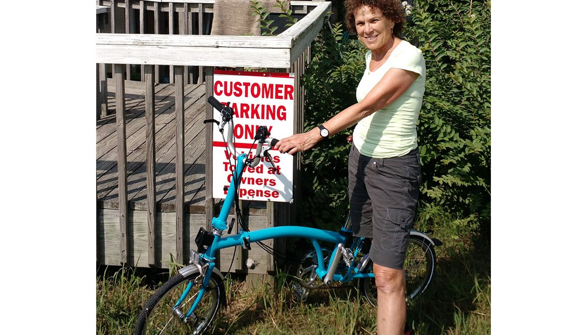 Woman Stands Next To Her Foldable Bike And Poses Next To Sign About Customer Only Parking Towing Sign, Livable Communities, Biking Infrastructure