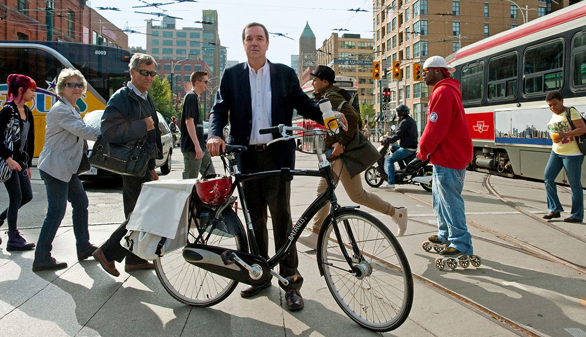 Gil Penalosa Stands In A Busy City Street With His Bike, Commuters On The Street, Buses, Livable Communities, Biking Infrastructure