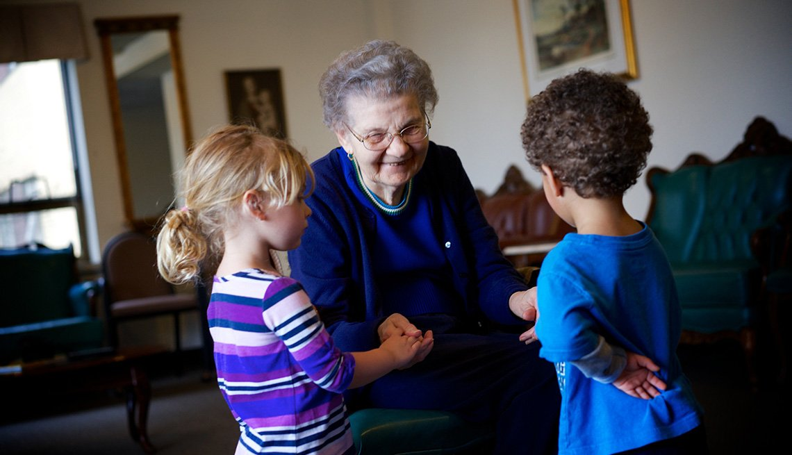Providence Mount St Vincent Assisted Living, Seattle, Elderly Woman Shakes Hands And Talks To Two Young Children, Indoors, Room, Livable Communities, Build Bonds Across Generations