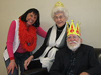 """Pat Raumbaugh, the """"Play Lady,"""" and an older woman and man wearing royal crowns."""