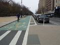 A sidewalk, protected bicycle lane, marked crosswalk and roadway, Prospect Park West, Brooklyn, New York