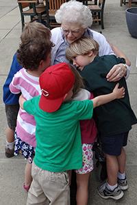 Five preschoolers hug an older woman at Maple Knoll Village.