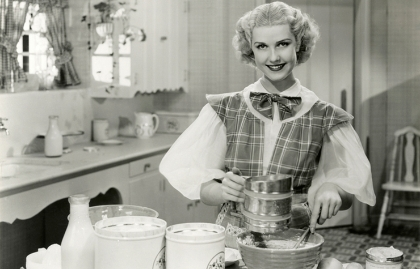 Vintage, 1950s-era woman dressed up and baking in her suburban kitchen.