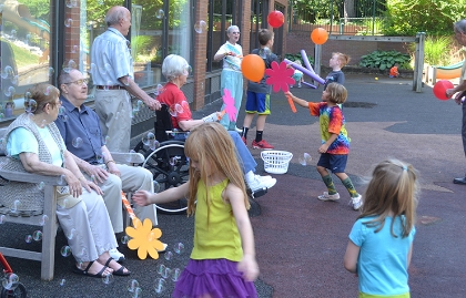 Pre-school students blow bubbles with senior citizens at the Maple Knoll Village Retirement Community in Ohio