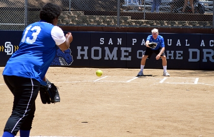 A San Pasqual Academy student and coach practice softball pitching.