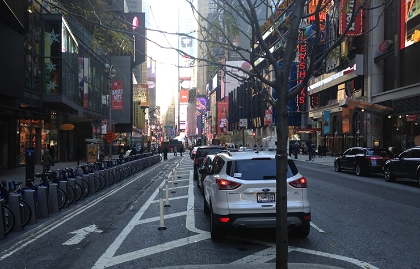 A sidewalk, protected bicycle, parking and roadway in Times Square, New York City