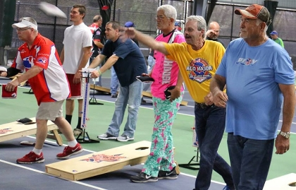 Young, middle-aged and older men playing cornhole.