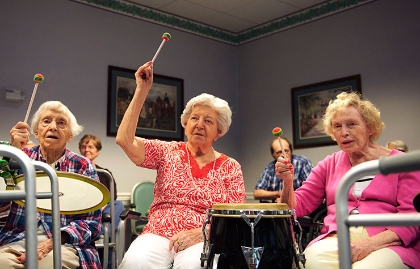 Three elderly women in a drumming class.