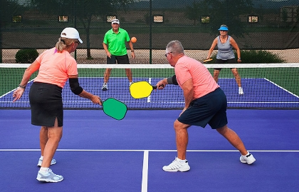 Two older men and two older women play pickleball.