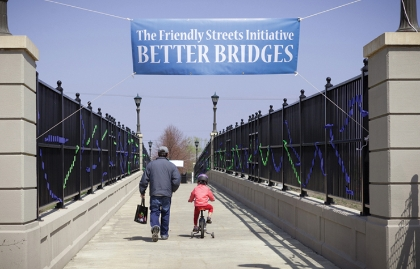 A man traveling by foot  and a young girl on a bicycle cross a pedestrian bridge that's decorated with a banner for the Friendly Streets Initiative Better Bridges