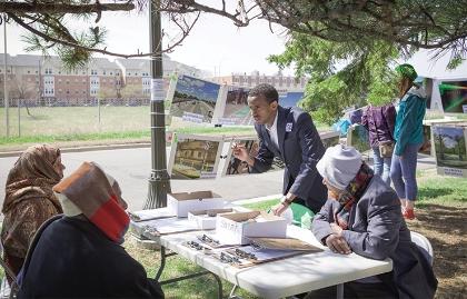 Community leader Isaak Rooble talks to three women about neighborhood improvements