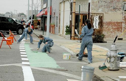 Painting a green bicycle lane for a pop-up demonstration on Broad Street in Memphis, Tennessee