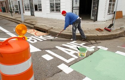 Artist and volunteer Tom Clifton helps paint the event's pop-up bike lane on Broad Avenue in Memphis, Tennessee