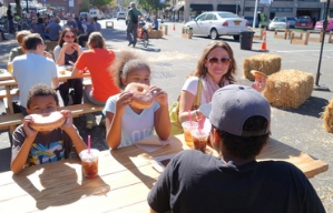 People eat very large Voodoo Doughnuts in a temporary plaza in Portland, Oregon