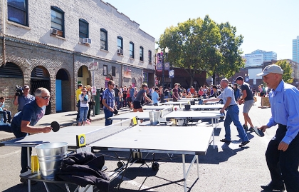 Portland Mayor Charlie Hales plays ping-pong in an outdoor plaza