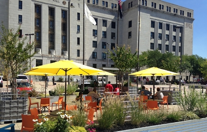 Yellow garden umbrellas, small tables and orange chairs at a pop-up plaza demonstration in Camden, New Jersey