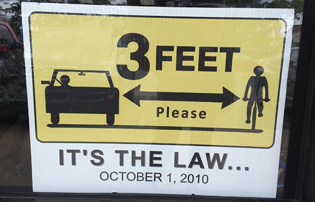 A sign shows that the law requires vehicles to stay 3 feet away from the bicyclists at right