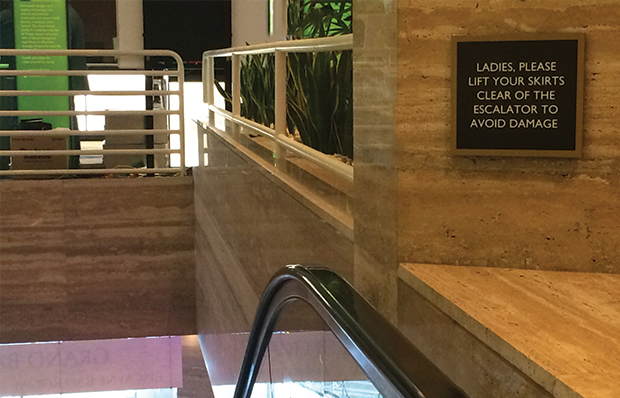 A sign instructs women to lift their skirts clear of an escalator to avoid damage