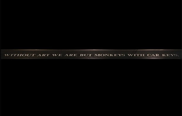 A sign hanging from a hallway ceiling says Without Art We Are But Monkeys With Car Keys