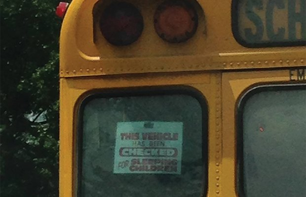 A school bus with a sign that says This Vehicle Has Been Checked for Sleeping Children