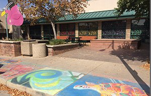 A flamingo sculpture and sidewalk chalk art in Loveland, Colorado