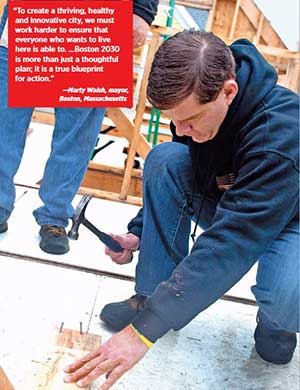 Boston Mayor Marty Walsh hammers nails on a home construction site.