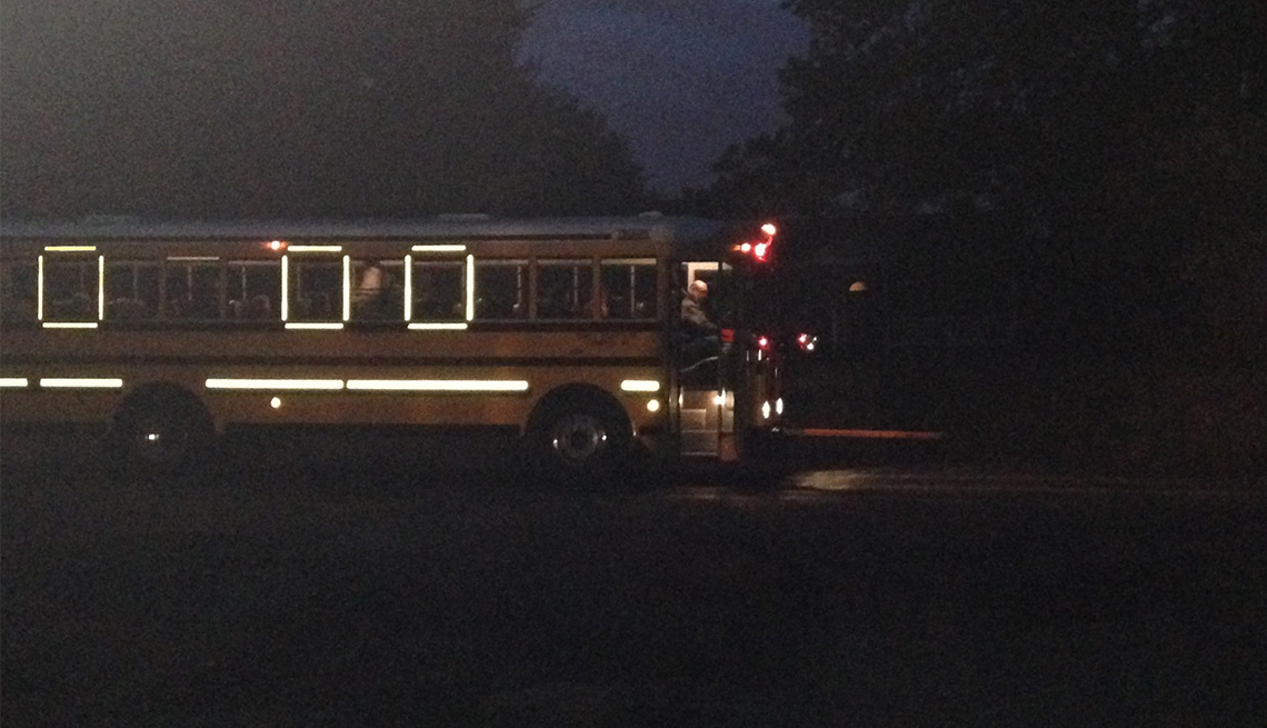 A high school-bound bus in Anne Arundel County, Maryland, picks up students in the 6:41 a.m. darkness of an October morning