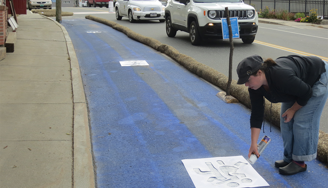 A woman uses a stencil and white spray paint to add markings to the Blue Lane.
