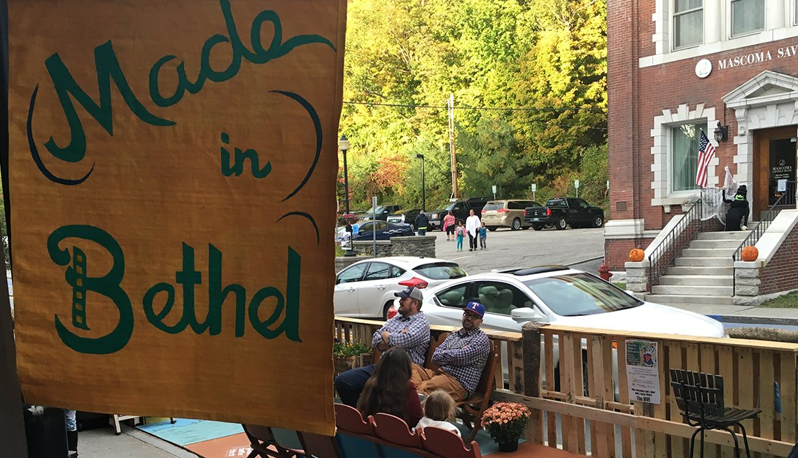 Visitors sit in a parklet that's decorated with a sign that reads Made in Bethel