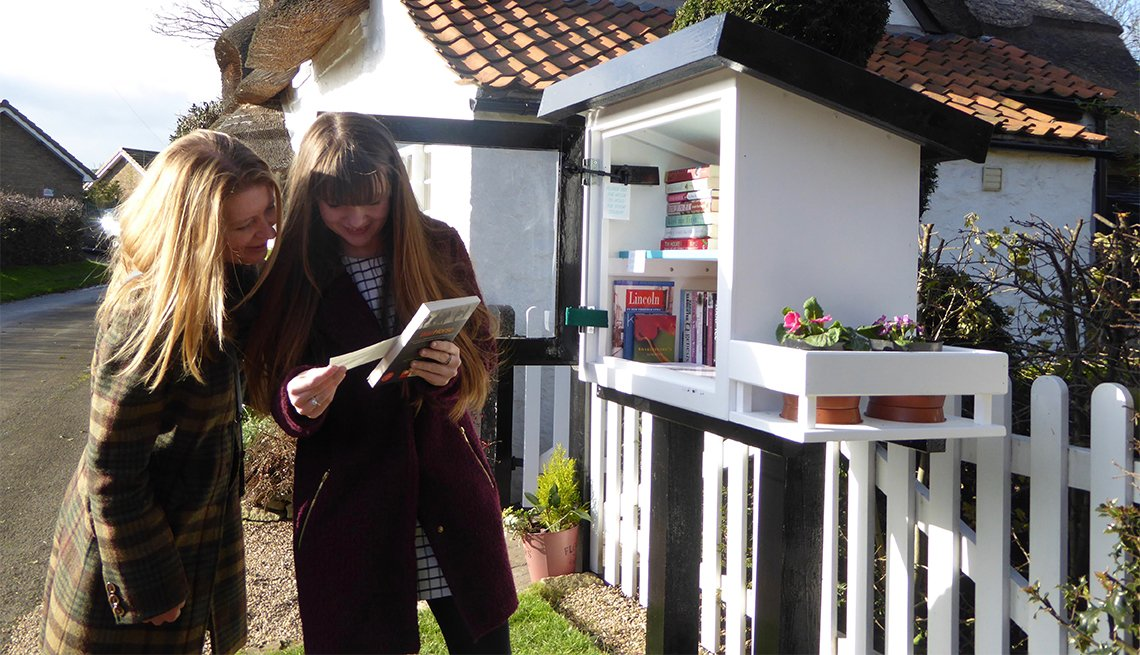 Two women look at books at a Little Free Library in Appleby, United Kingdom
