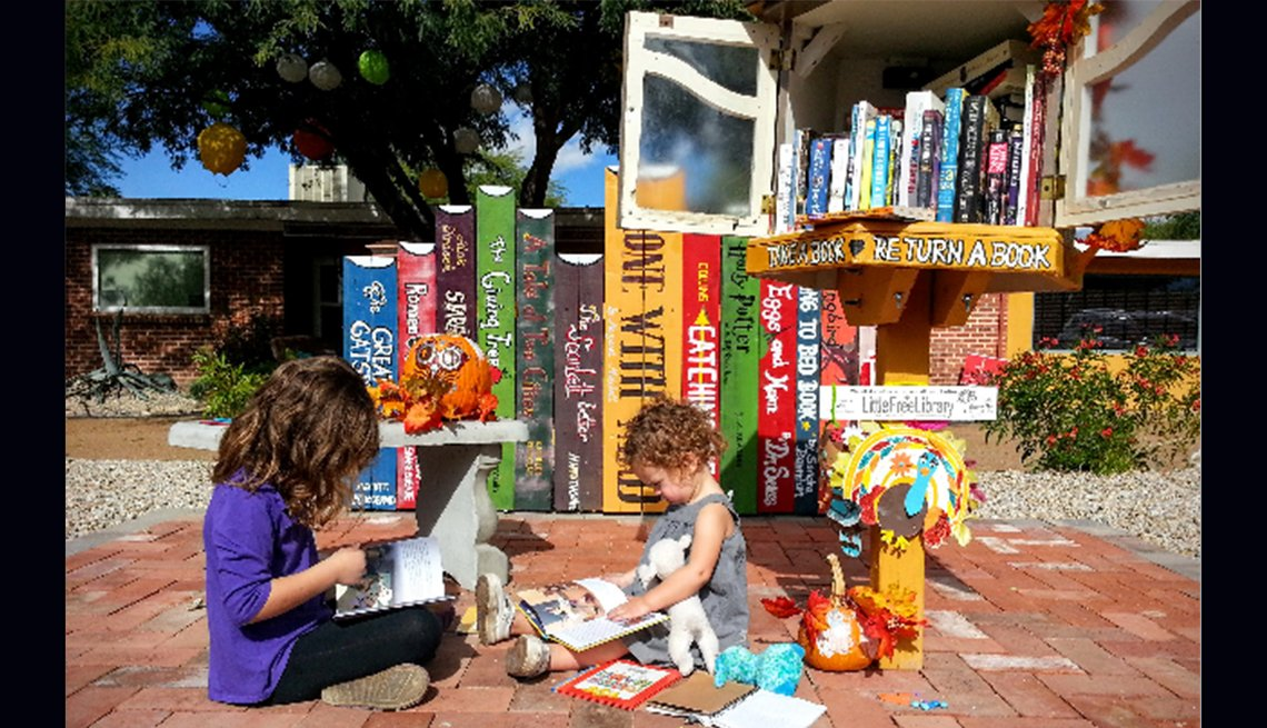 A young girl and a girl toddler sit on a brick path and read books in front of a little library.