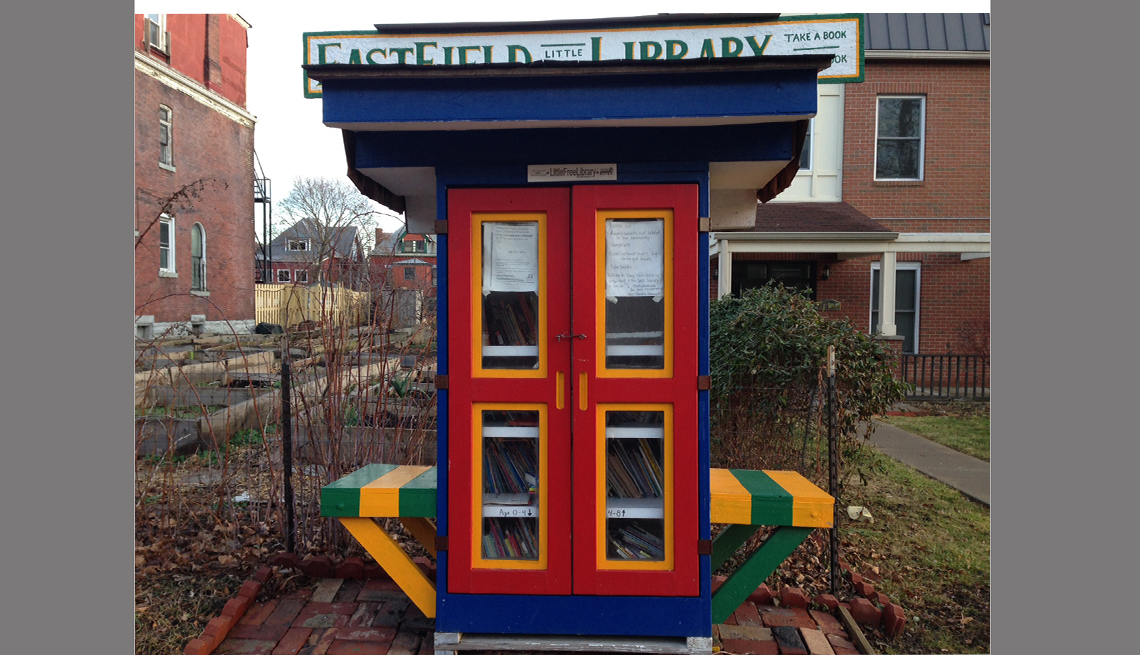 A library-sponsored Little Free Library has seating for two.