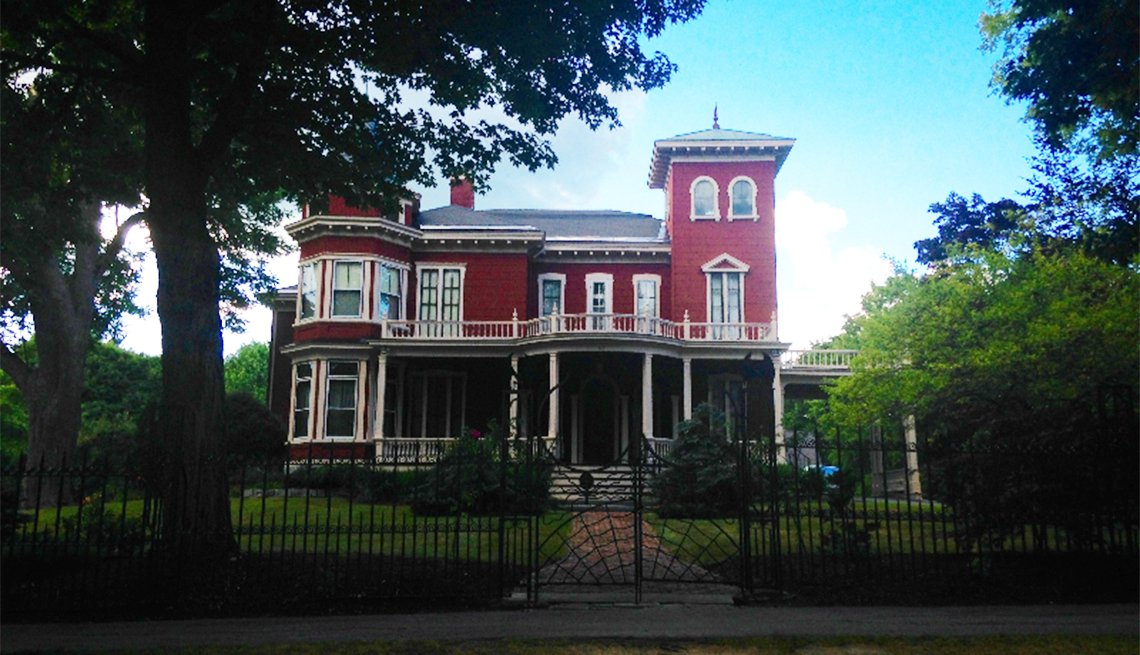 The Bangor, Maine, home of author Stephen King features a red exterior, a turret and an insect-themed iron gate.
