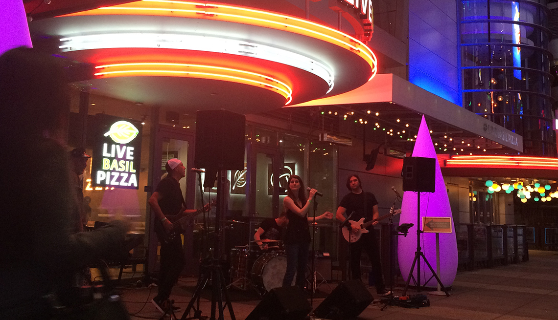 A rock band performs on the sidewalk outside Smashburger at LA Live in Los Angeles