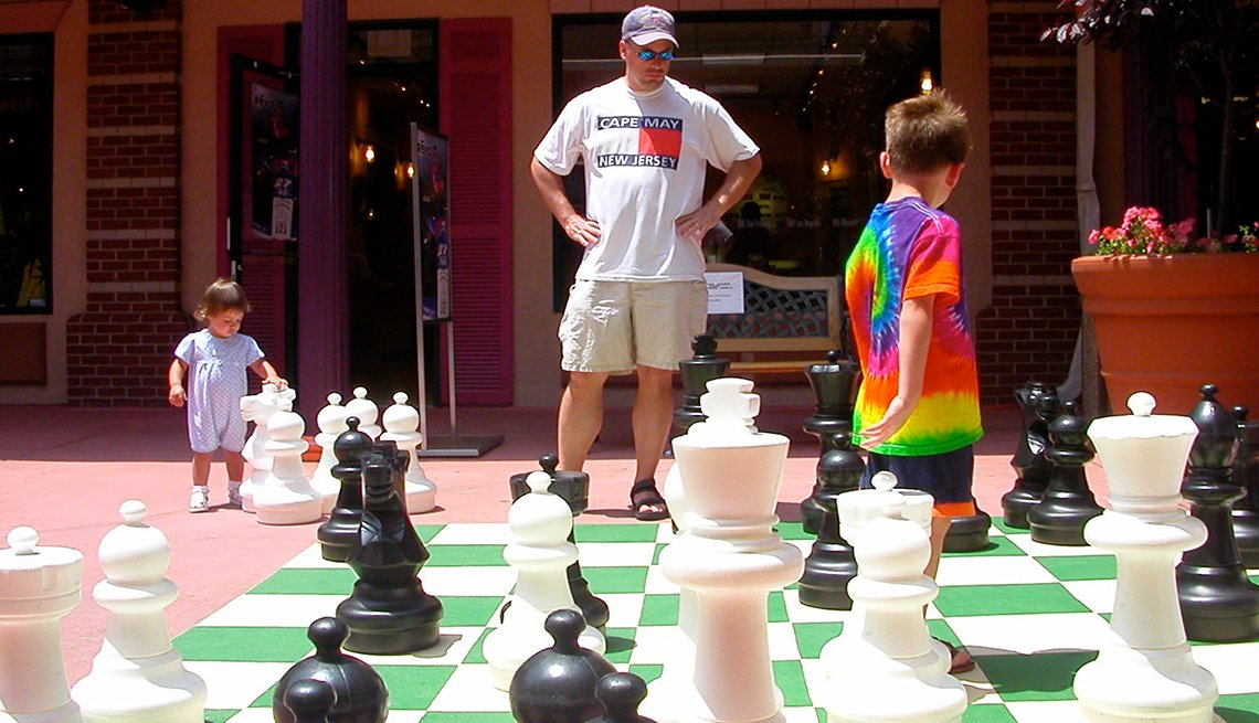 A dad and two children play giant chess in Rehoboth, Delaware
