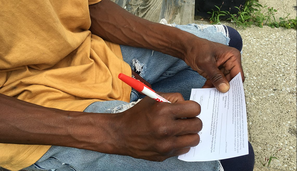 A resident of Flint, Michigan, completes a form allowing for the replacement of the main water pipe to his home.