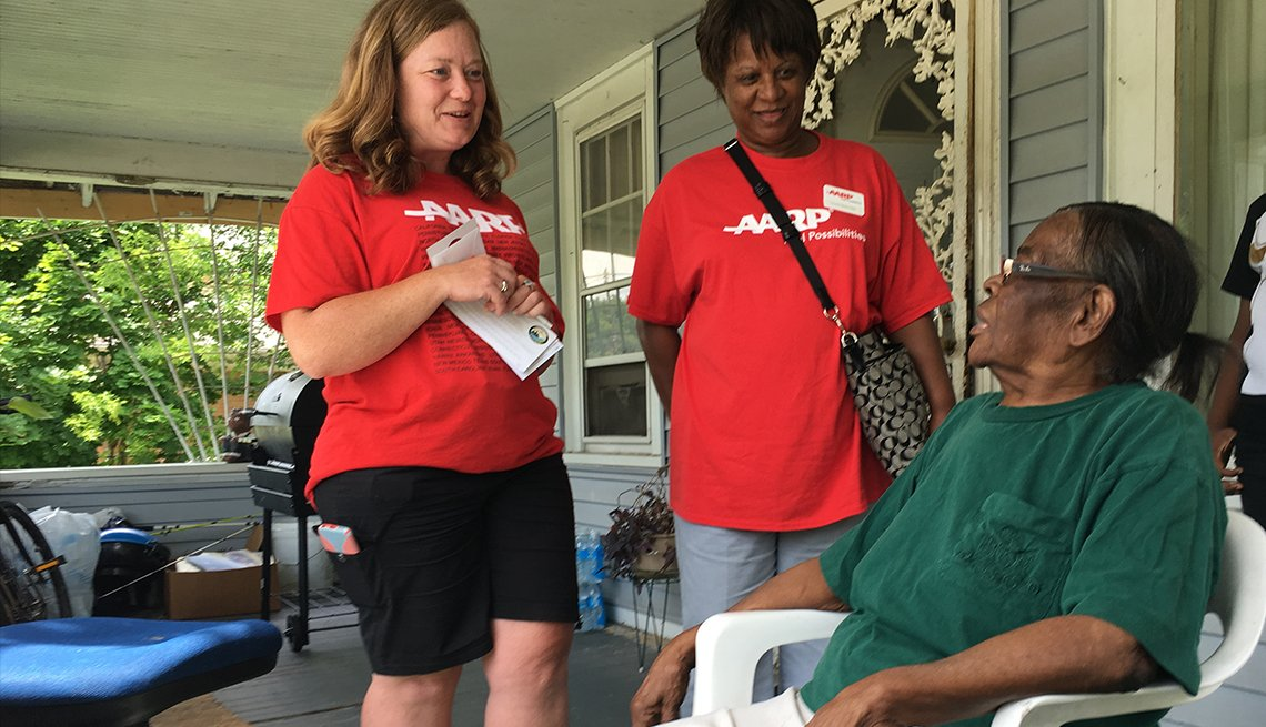 Two women representing AARP Michigan visit with a Flint resident who's sitting on her front porch.