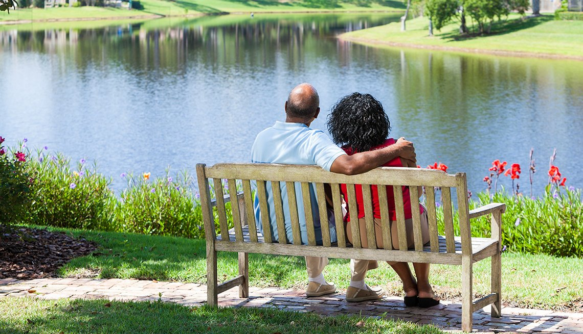 African American couple sitting together beside lake.