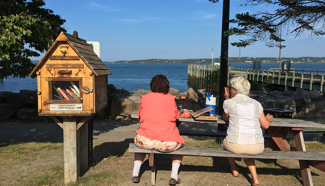 Two women sit at a picnic table in Eastport, Maine, with a view of the water and a Little Free Library display