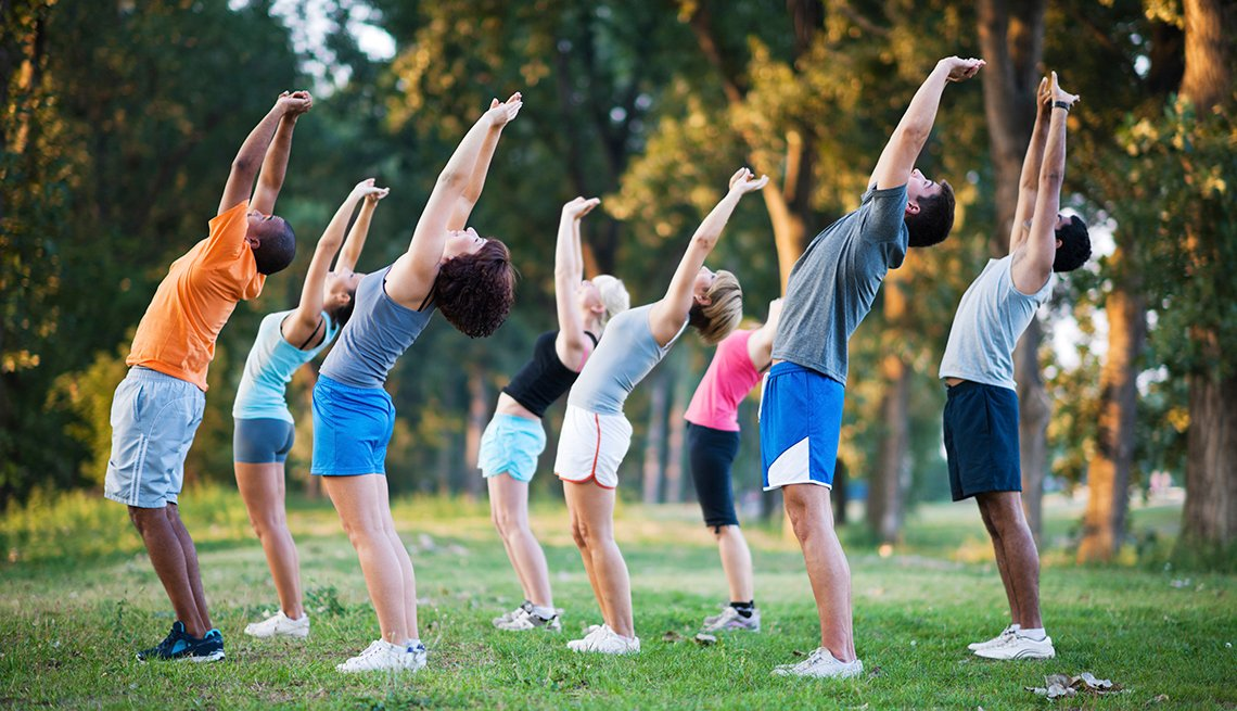 Group of people stretch in a park, AARP Livable Communities, A Livable Lesson
