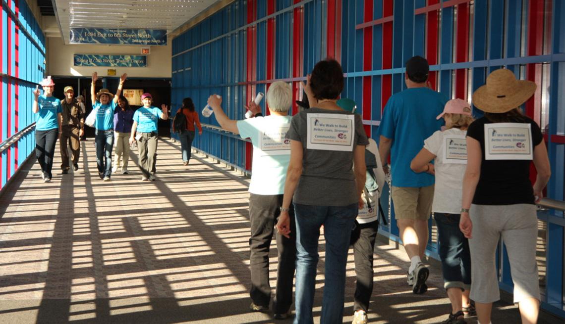 Dos grupos que participan en una caminata de 5 kilómetros para promover el bienestar se encuentran dentro del sistema de pasillos elevados de Minneapolis