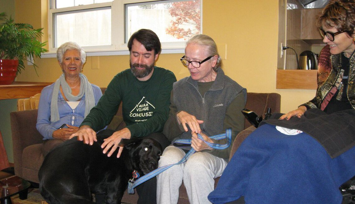 Neighbors, Co-Residents Sit On Sofa And Play With Dog, Co-Housing, AARP Livable Communities, More About Housing