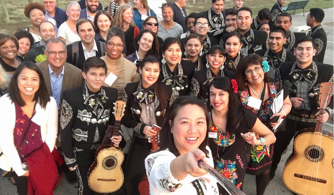 Attendees at the 2017 AARP Livable Communities pose with a mariachi band in the Trinity Groves area of Dallas, Texas